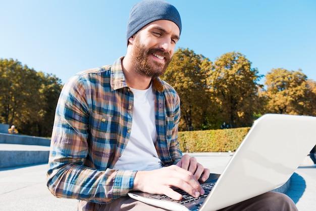 Internet sans fil rend la recherche un jeu d'enfant ! vue grand angle du beau jeune homme barbu souriant tout en travaillant sur un ordinateur portable