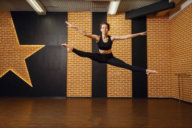 Interprète féminine de danse contemporaine, saut en mouvement, formation en studio. danseur sur séance d'entraînement en classe, ballet moderne, danse d'élégance, exercice d'étirement