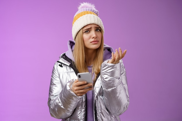 Interrogé compliqué jolie petite amie blonde recevoir un message étrange regard perplexe confus levant la main en haussant les sourcils de levage ne peut pas comprendre la signification tenant un smartphone, fond violet.