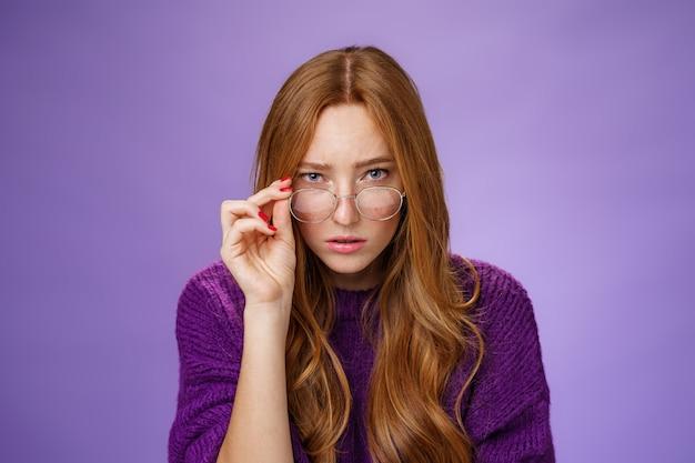 Interrogée et incertaine, une jolie femme détective intelligente aux cheveux roux semblant suspecte sous le front, enlevant des lunettes et regardant la caméra de manière douteuse et incertaine sur fond violet.