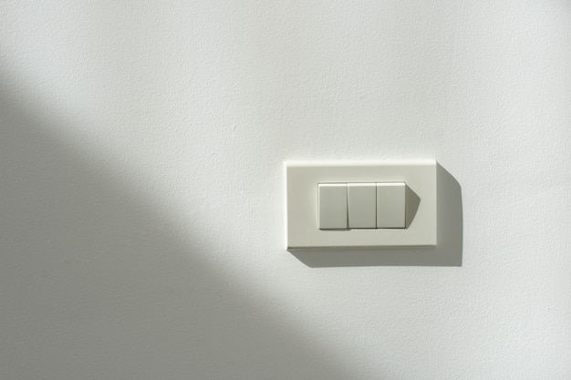 Interrupteur blanc sur un mur blanc avec contraste de lumière et d'ombre.