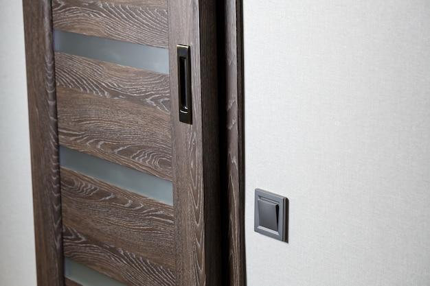 Interrupteur à deux clés de couleur grise près de la porte, interrupteur mécanique en plastique. l'interrupteur d'éclairage est installé après réparation. concept d'économie d'énergie. fermer l'interrupteur d'éclairage