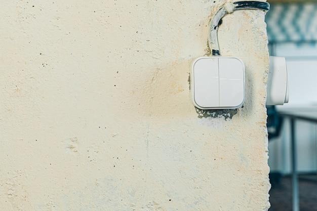 Interrupteur d'éclairage à l'ancienne sale sur mur rugueux