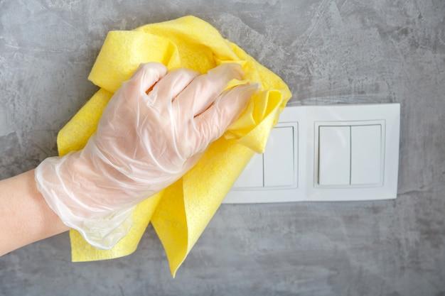 Interrupteur d'éclairage propre à la main avec un chiffon sur un mur de béton gris. femme au gant désinfectant les surfaces avec un chiffon jaune. le nouveau coronavirus covid normal dans le nettoyage. désinfection des surfaces.