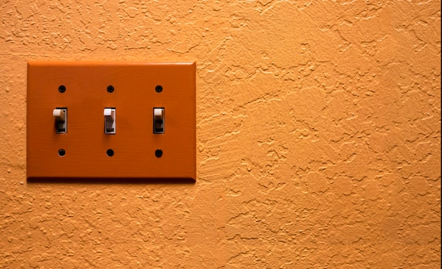 Interrupteur électrique vintage sur mur orange rétro
