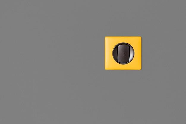 Interrupteur simple sur mur gris. touches en graphite et cadre jaune vif.