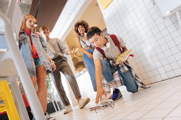 L'intimidation à l'école. seul garçon asiatique qui s'étend de la main tout en prenant des livres du sol