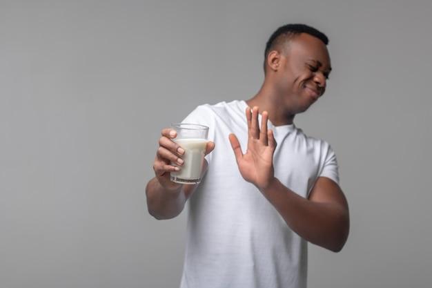 Intolérance au lactose. jeune homme noir adulte avec grimace refusant le verre de lait faisant des gestes en se tenant debout en studio