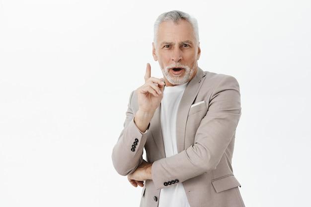 Intrigué beau vieil homme en costume levant le doigt, ont une excellente idée