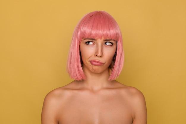 Intrigué jeune femme aux cheveux roses attrayante avec un maquillage naturel tordant sa bouche tout en regardant confusément vers le haut, posant sur un mur de moutarde avec des épaules nues