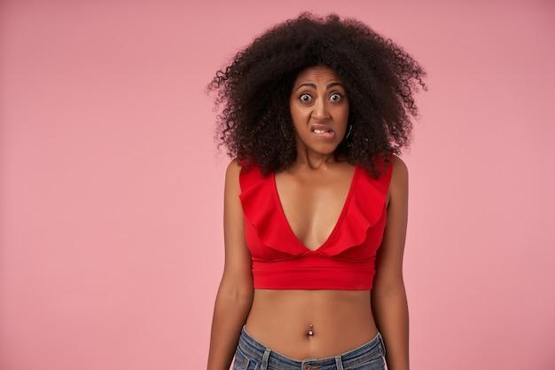 Intrigué jeune femme à la peau sombre avec des cheveux bouclés portant un haut rouge et un jean, posant sur le rose avec les mains vers le bas, regardant avec le visage confus et le front plissé tout en mordant le dessous