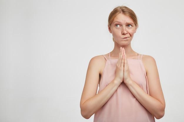 Intrigué jeune femme rousse séduisante avec maquillage naturel gardant les mains levées ensemble et tordant sa bouche tout en regardant confusément de côté, isolé sur fond blanc