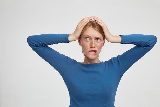 Intrigué jeune femme séduisante avec maquillage naturel tenant les mains levées sur sa tête et mordant ses lèvres avec inquiétude, debout sur fond blanc en chemisier bleu