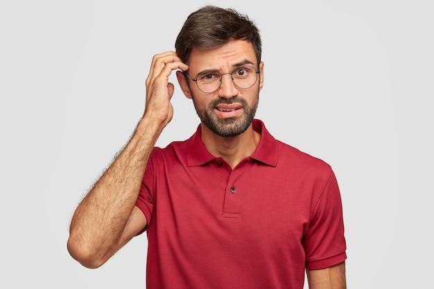 Intrigué jeune homme émotionnel posant contre le mur blanc