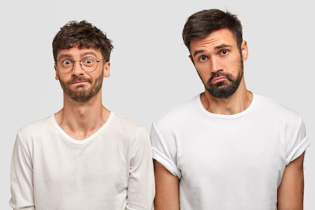 Intrigué et triste, deux jeunes gars barbus se tiennent étroitement l'un à l'autre, expriment des émotions négatives, regardent avec perplexité, portent des vêtements décontractés blancs