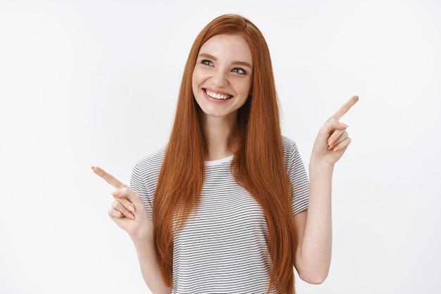 Intriguée amusée belle étudiante rousse yeux bleus en t-shirt rayé d'été pointant sur le côté regarder à gauche amusé cueillette produit, prise de décision d'achat, mur blanc