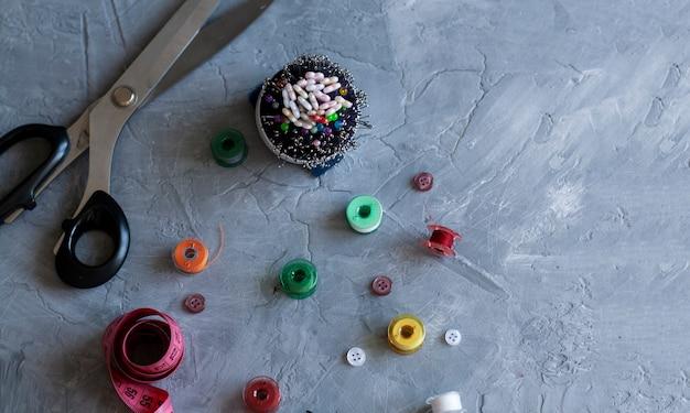 Un inventaire sempstress: ruban à mesurer, boutons, aiguilles, fils et ciseaux.