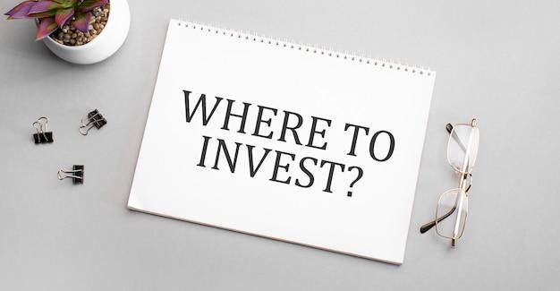 Où investir est écrit dans un cahier blanc à côté d'un crayon, de verres à cadre noir et d'une plante verte.
