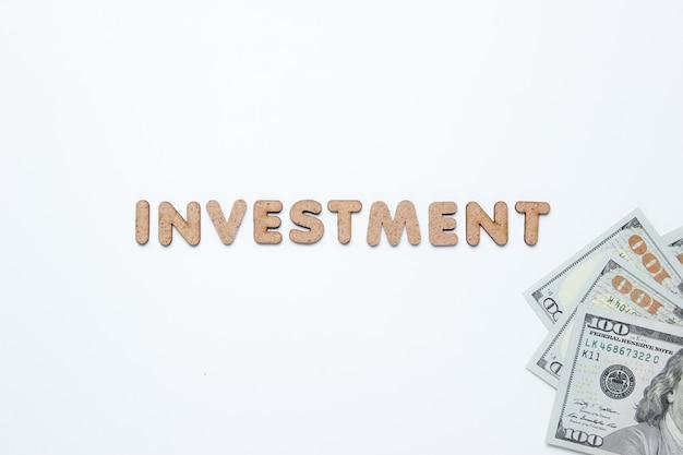 Investissement de mot et billets d'un dollar sur une surface blanche.
