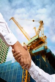 Investisseur au chantier de construction serrant la main