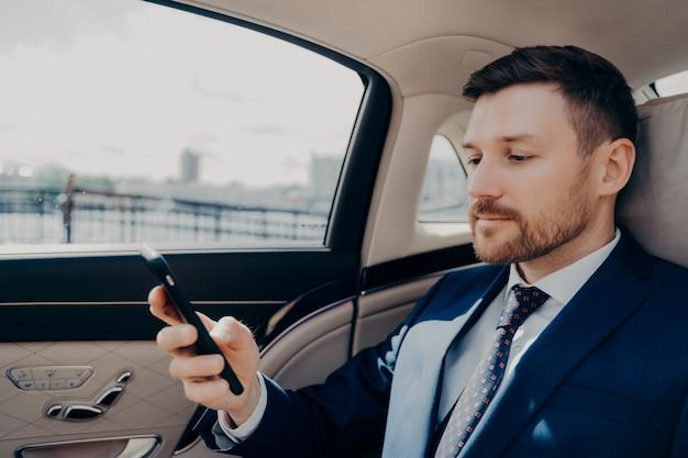Investisseur barbu en costume bleu vérifiant les messages téléphoniques et les notifications, recevant des nouvelles troublantes sur son entreprise, réfléchissant et décidant de son prochain mouvement tout en conduisant à l'arrière d'une voiture confortable