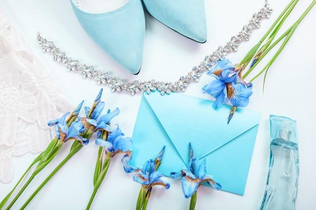 Invitation de mariage entourée de fleurs, chaussures de mariée, parfum et bijoux