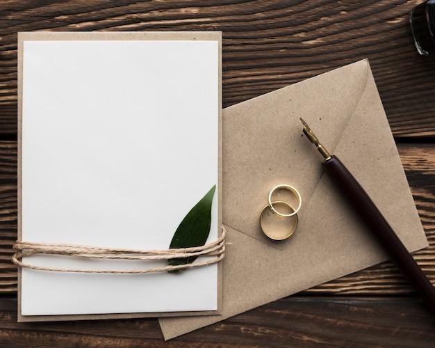 Invitation de mariage sur table avec bagues de fiançailles