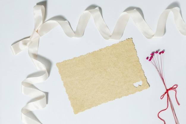 Invitation de mariage vierge à côté d'un ruban et de petites fleurs rouges sur fond blanc