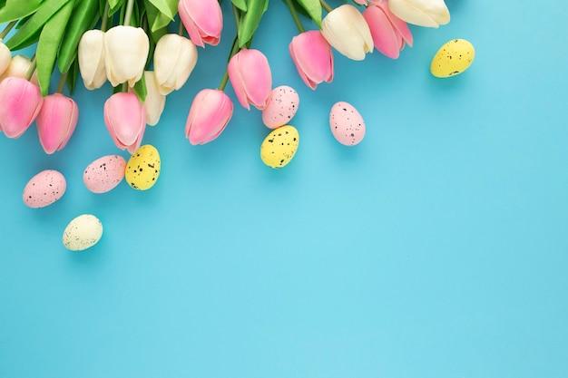 Invitation de pâques avec des tulipes sur fond bleu avec espace copie