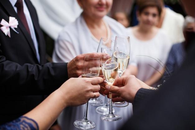 Les invités accrochent des verres au dîner weding