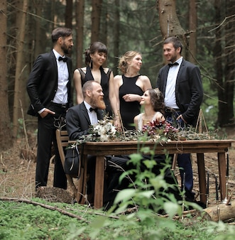 Des invités et un couple de jeunes mariés près de la table de pique-nique dans les bois.