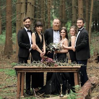 Des invités et un couple de jeunes mariés près de la table de pique-nique
