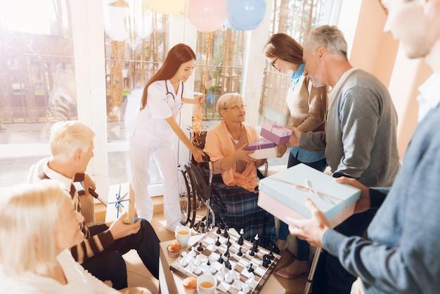 Des invités offrent des cadeaux à une fête d'anniversaire pour femme âgée