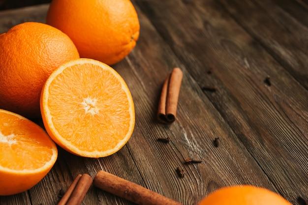 Ipe juteuses oranges sur un ancien espace de copie de table en bois. moitiés d'oranges. bâtonnets de cannelle