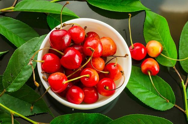 Ipe sweet cherry dans une assiette sur un fond noir avec des feuilles