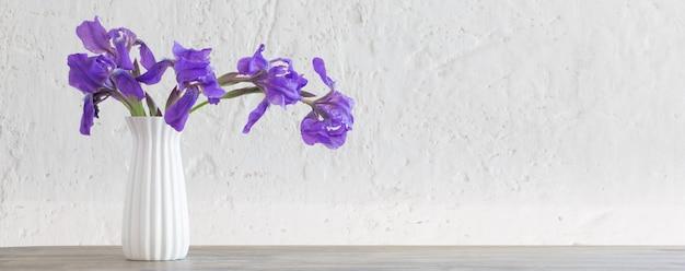 Iris dans un vase sur fond blanc vieux mur