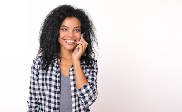 Irrésistible fille afro-américaine en chemise de flanelle tient un smartphone entendre son oreille gauche, souriant et regardant directement la caméra