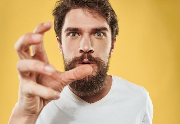 Irritable jeune homme avec barbe sur vue recadrée jaune.