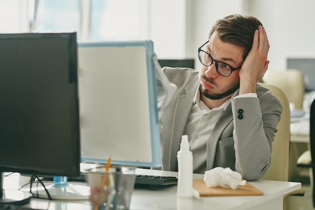 Irrité jeune homme d'affaires à lunettes assis au bureau