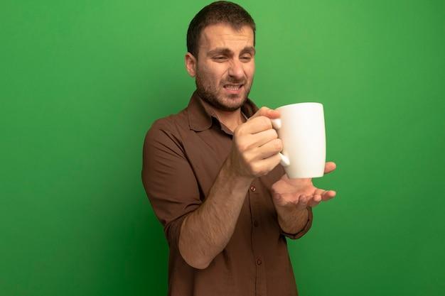 Irrité jeune homme isolé sur la tenue verte et regardant la tasse de thé en gardant la main dans le mur d'air