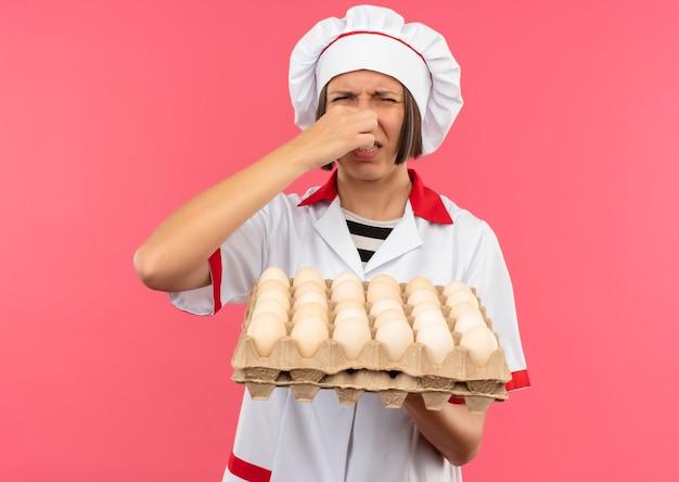 Irritée jeune femme cuisinier en uniforme de chef holding carton d'oeufs et son nez isolé sur rose