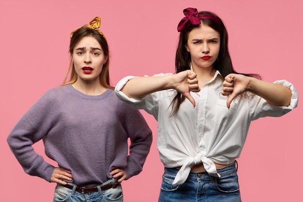 Irritée jeune femme fronçant les sourcils en gardant les mains sur la taille étant têtue posant à côté de son amie en colère agacée qui montre les pouces vers le bas n'aiment pas le geste comme signe de désapprobation