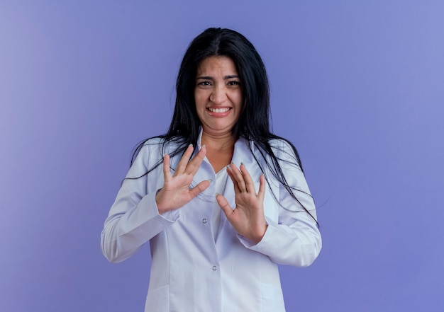 Irritée jeune femme médecin portant une robe médicale à ne faire aucun geste