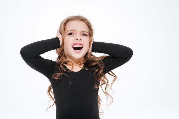 Irritée petite fille a couvert ses oreilles par des mains et des cris