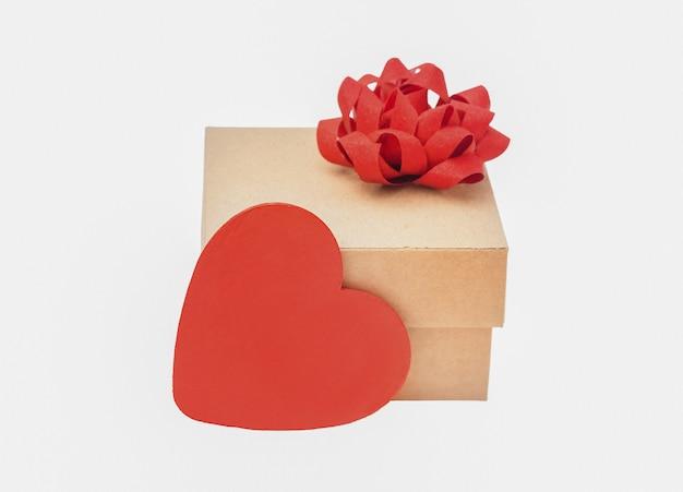 Isolat de cadeau de boîte en carton. cadeau avec noeud rouge et coeur rouge sur fond blanc
