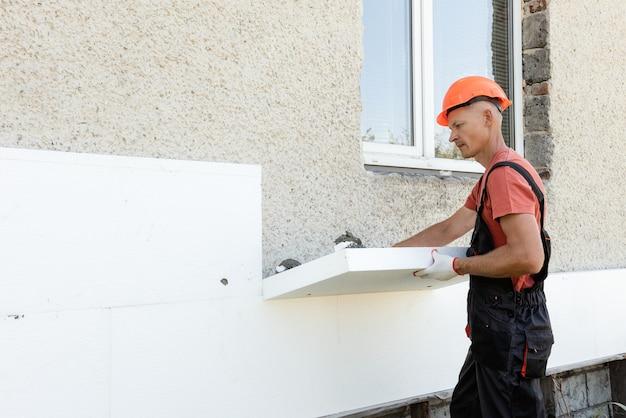 Isolation de la maison avec polyfoam. le travailleur installe une planche de polystyrène sur la façade.