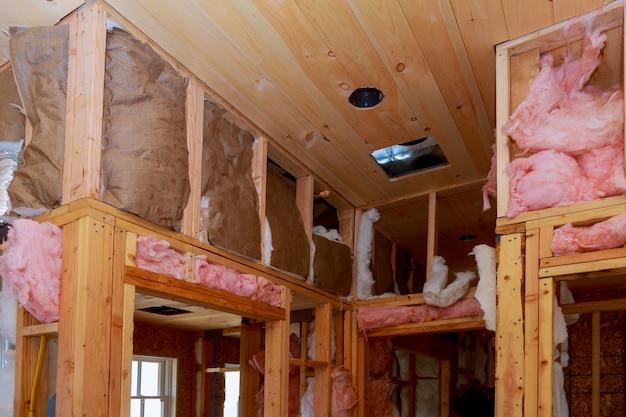 Isolation thermique du mur intérieur avec de la laine minérale dans une maison en bois, bâtiment en construction