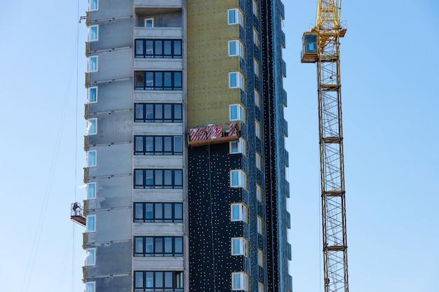 Isolation thermique d'un immeuble résidentiel de plusieurs étages en construction avec une grue à tour.