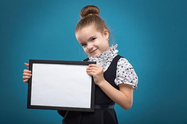 Isolé sur bleu, attrayant enfant caucasien tenir grosse affiche vide