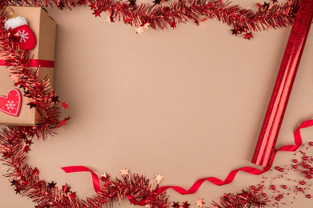 Isolé . un cadeau emballé dans du papier kraft, avec un ruban rouge sur lequel reposent des bas de bonbons, des mitaines et un cœur de papier, est entouré de tinsel rouge. vacances.